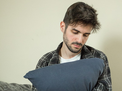 Depressed man hugging pillow looking down considering calling hotline
