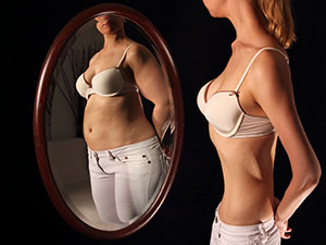 Woman with anorexia looking in mirror