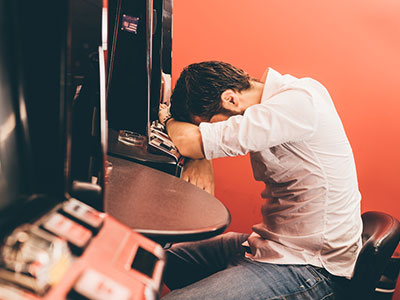 Man slumped on slot machine, gambling loss