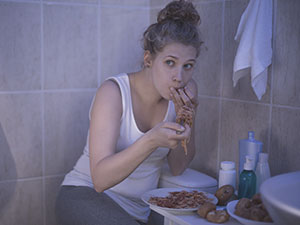 Girl binging on food in bathroom