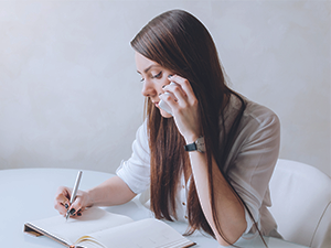 woman making a phone call and taking notes