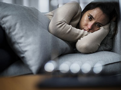 Woman laying in bed looking anxious